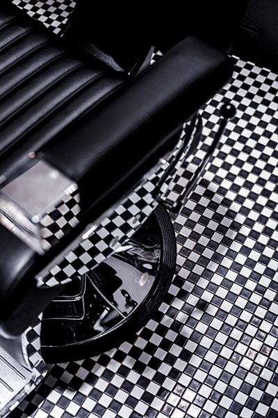 Fauteuil de barbier noir en cuir posé sur carrelage à damier noir et blanc.