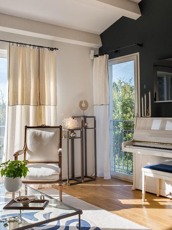 Salon du projet MC&G à Bormes Les Mimosas, on peut y voir un fauteuil blanc ainsi qu'un piano blanc