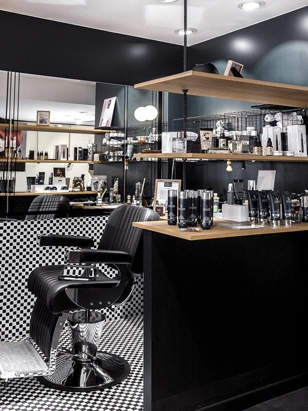 Fauteuil de barbier en cuir noir posé sur une faïence à damier noir et blanc