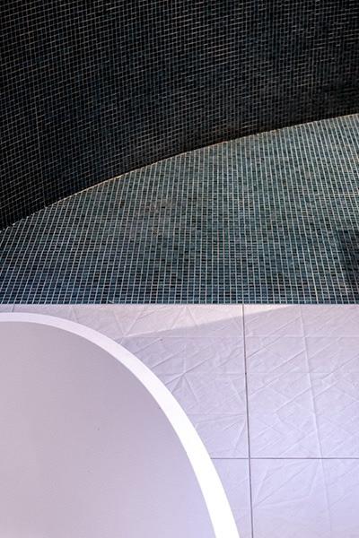 Carrelage au sol blanc du côté baignoire et faïence verte du côté douche à l'italienne