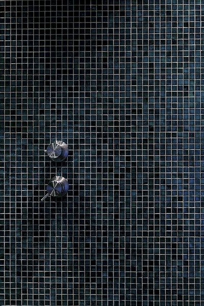 plan serré de la faïence de couleur verte dans la douche à l'italienne du projet P&Br