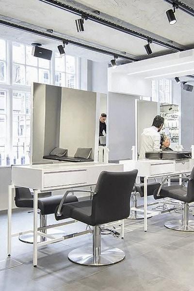 Coiffeuse blanche et fauteuil en cuir noir dans le salon de coiffure Mazella&Palmer à Londres