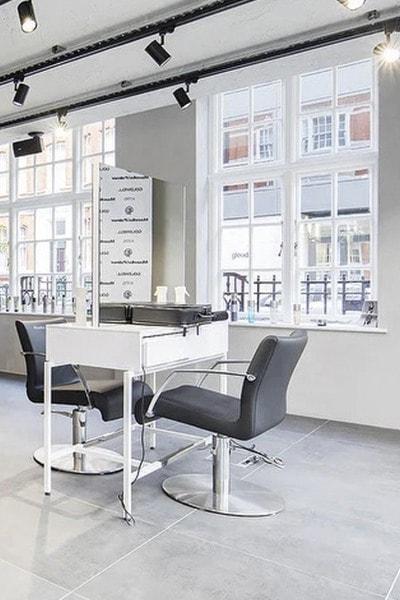 Coiffeuse face à face blanche et fauteuil en cuir noir dans le salon de coiffure Mazella&Palmer à Londres