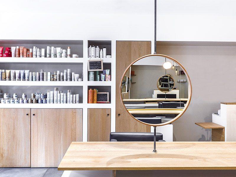 Miroir rond en bois dans le salon de coiffure Un autre regard au Lavandou
